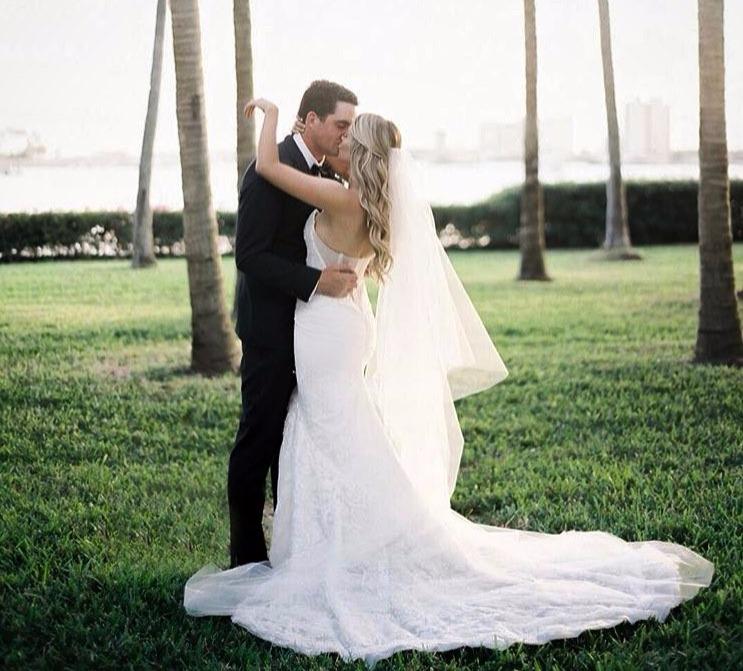 Keegan Bradley kissing his bride Jillian Stacey on their wedding day