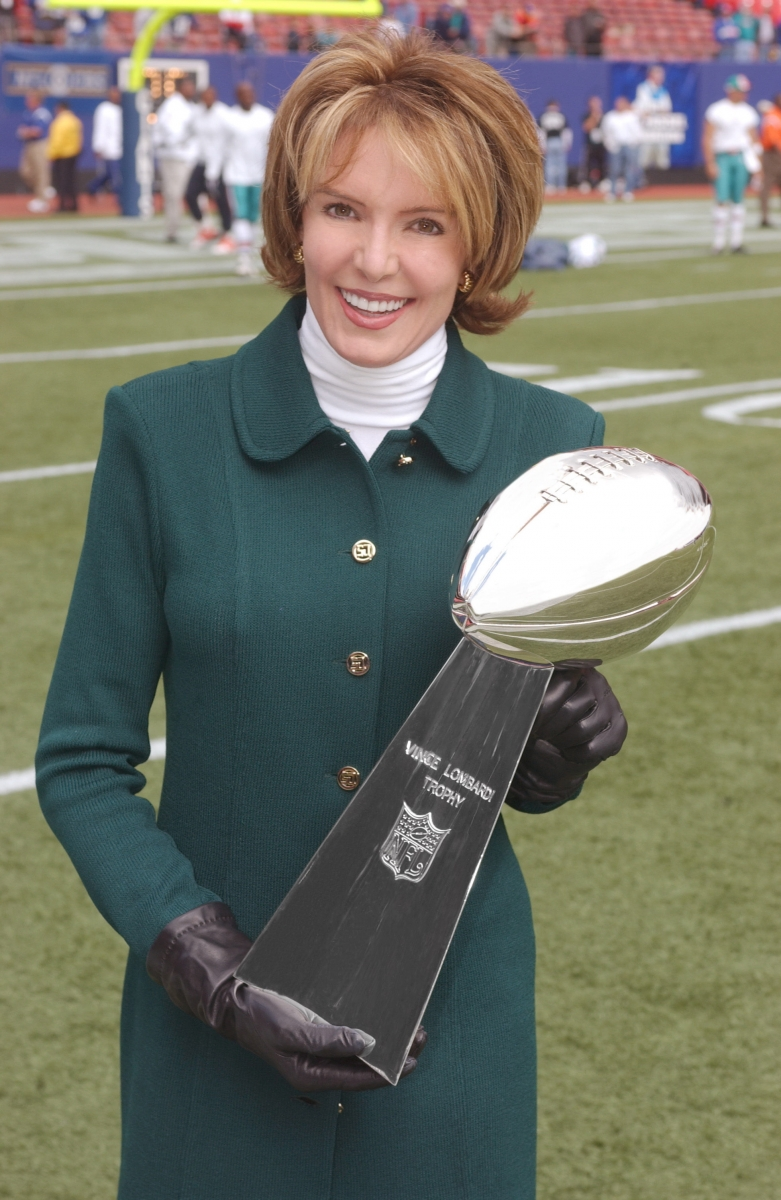 Lesley Visser carrying a Vince Lombardi trophy
