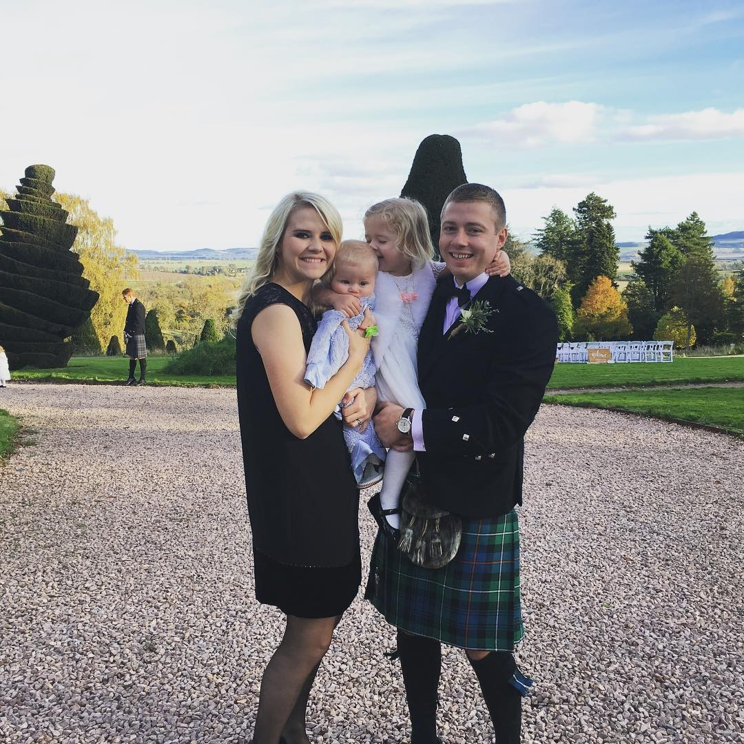 Elizabeth Smart with her husband Matthew Gilmour and her daughter posing for the camera. They are holding their daughters with a smile on their faces. They do make a great couple.