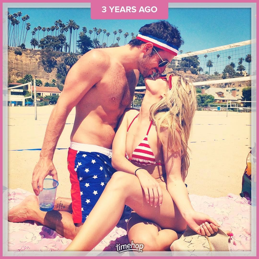 Kim Matula and her boyfriend Ben Goldberg are on the beach. Kim Matula is wearing a red and white striped bikini and shirtless Ben Goldberg is wearing blue shorts.
