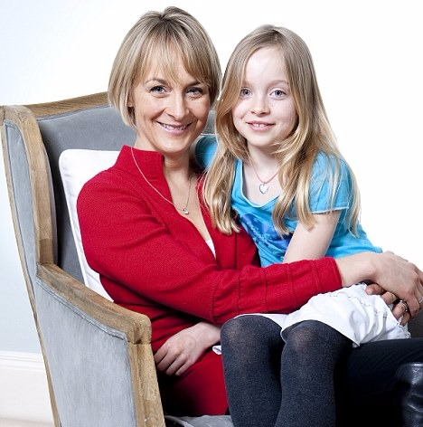 Louise Minchin sitting on an armchair with daughter Mia on her lap