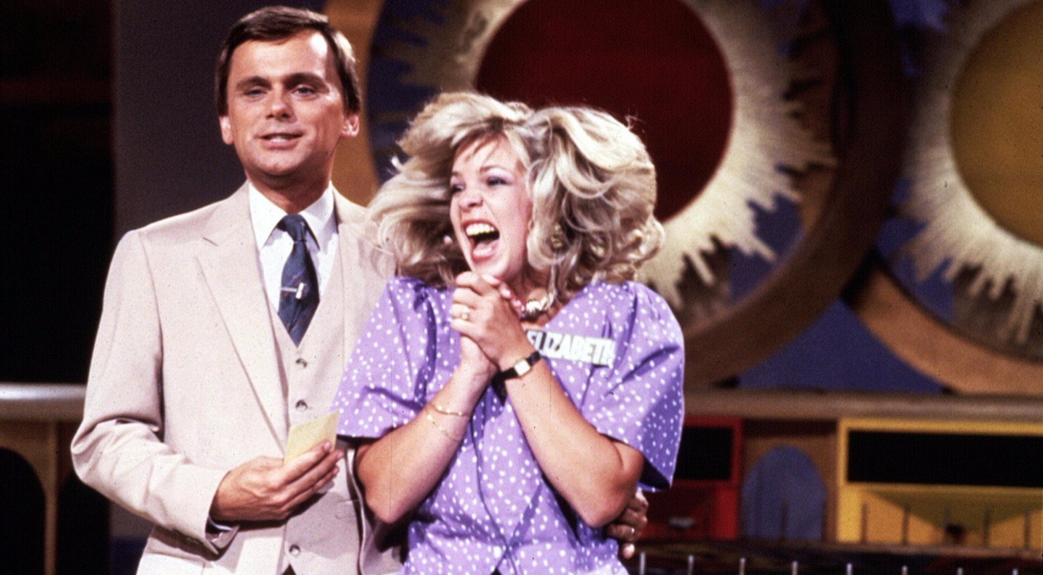 Young Vanna White clapping her hand in excitement on set of the show Wheel of Fortune. Pat Sajak and Vanna White have been rumored to have an affair but they have denied the allegation stating their relationship to be as that of a brother and sister.