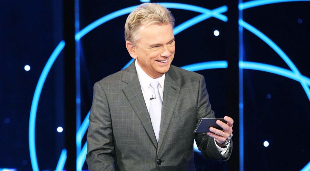 Pat Sajak is standing in front of a glowing background, holding a cheat on his left hand, slightly tilting his head and smiling to the audience.