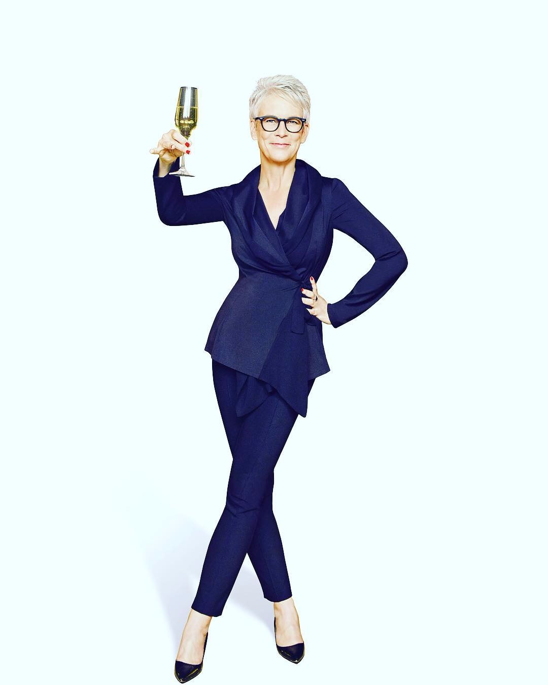 Jaime Lee Curtis is standing in a raising a toast posture in a formal dress, she is looking  bold and tall with her height of 5 feet 7 inches.