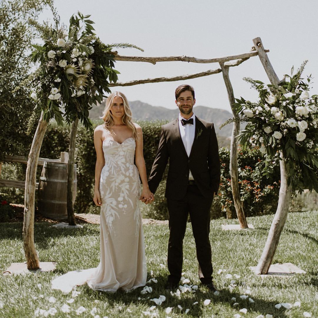 Josh Peck holding hands of his wife, Paige O'Brien on their wedding.