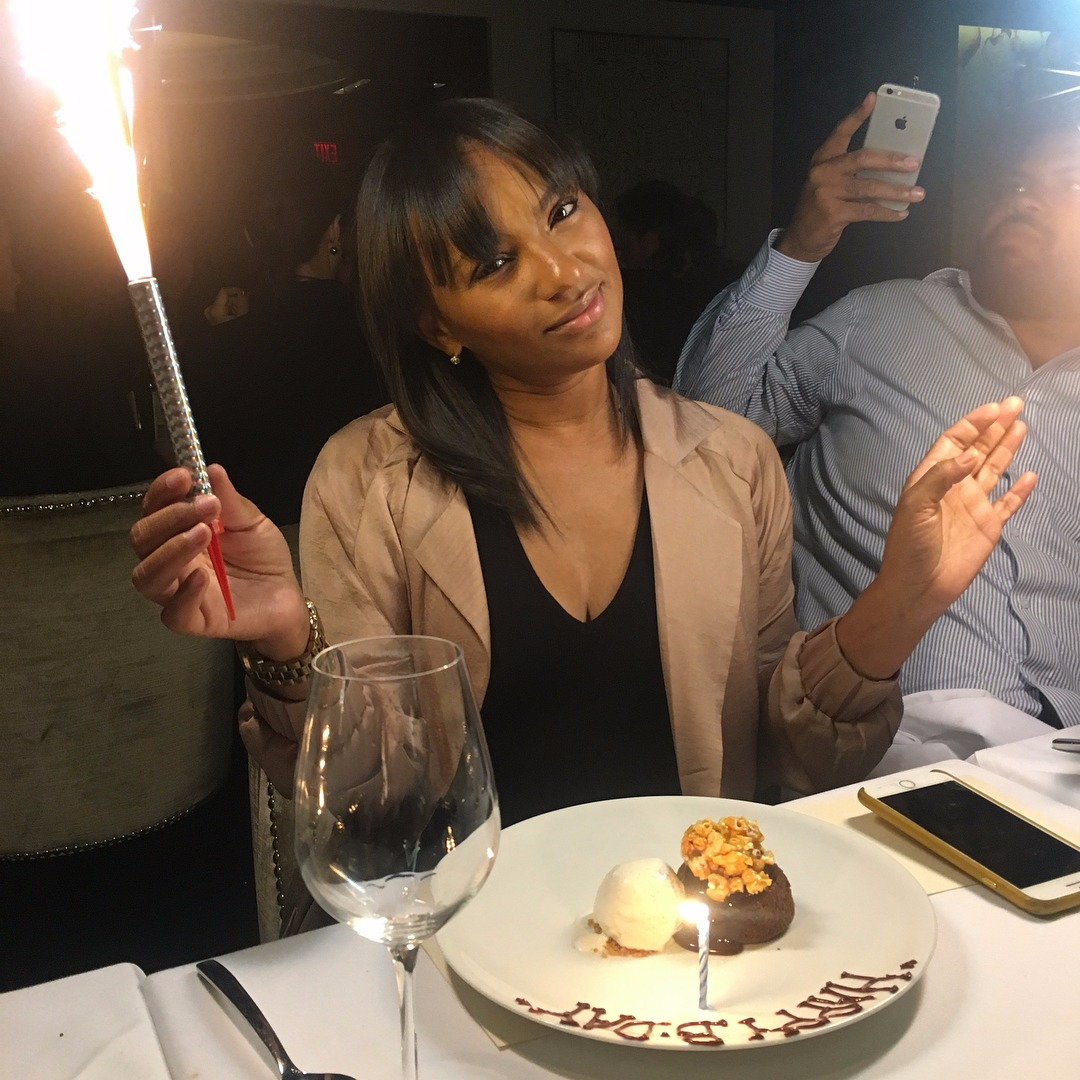 Tara Wallace is holding her birthday candle in her hand with a small cute cake placed in front of her. she is wearing a black top which is slightly revealing her cleavage and a nude colored jackect.