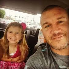 Randy Orton and Alanne Marrie Orton are smiling at the camera. Alanne is looking cute in pink dress.