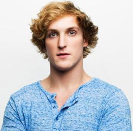 Logan Paul wearing a sky blue T-shirt is looking in front of the camera with a bold look and his hair colored blonde yellow with a shortwave cut.