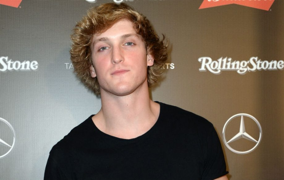 Logan Paul wears a black tee neck T-shirt and he is focusing to the camera giving a pose.