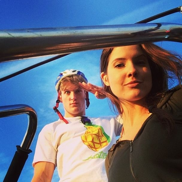 Logan Paul is with Amanda Cerny and they both are on an outing. Amanda is wearing a black sweatshirt and Paul is wearing a white T-shirt and a skateboard helmet.