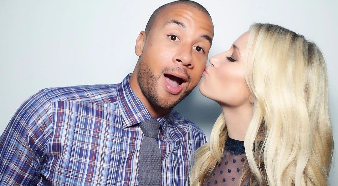 Kristine Leahy is kissing her boyfriend Aaron Hines on the cheek and Aaron Hines is opening his mouth in surprise.