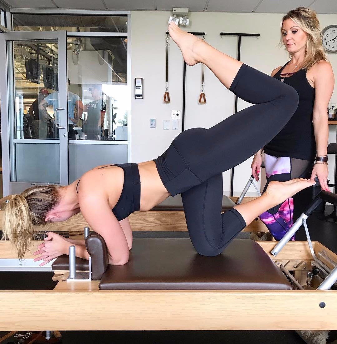 Kristine Leahy striking a Pilates pose while her trainer looks on