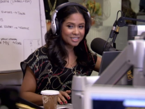 Angela Yee is at a radio station. She is wearing headphones and is talking on the mic. There's a cup of coffee on the table.
