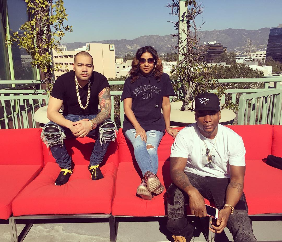 The Breakfast Club cast - DJ Envy, Angela Yee and Charlamagne Tha God are sitting on a red sofa.