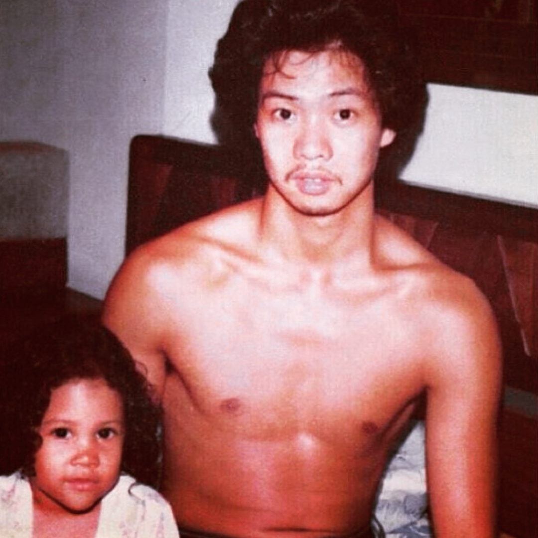 Young Angela Yee is sitting next to her father. Her father is shirtless.