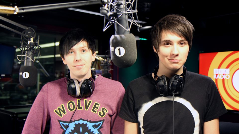 Phil Lester and Daniel Howell are at the BBC Radio 1 studio. They have big mics in front of them and are wearing headphones around their neck.