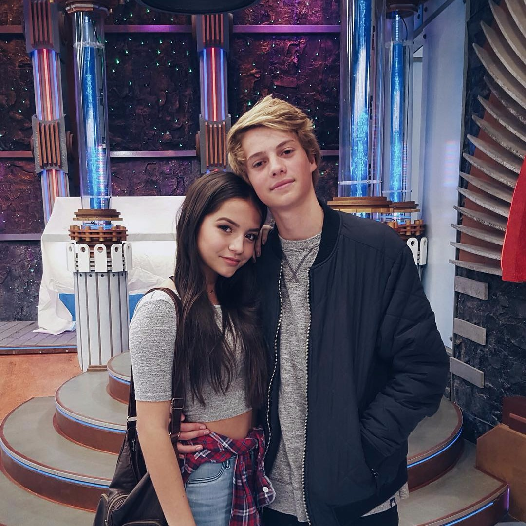 Isabela Moner cozying up to boyfriend Jace Norman as they pose for a picture. Isabela has tied her red-checked shirt around her waist and Jace is wearing a black bomber.