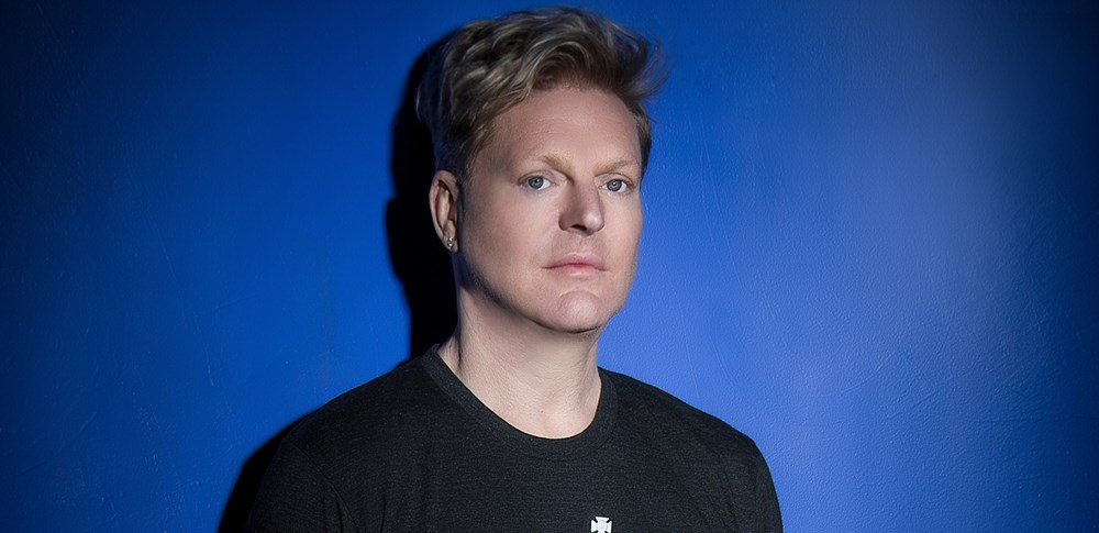 Andy Bell wearing a black t-shirt. There is a blue blackground.