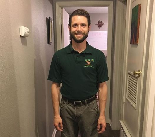 Danny Pintauro standing in front of the open door. He is smiling and wearing a black shirt.