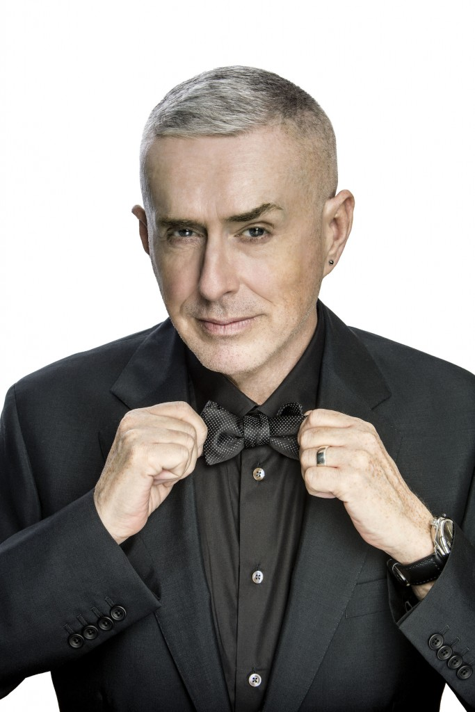 Holly Johnson giving a pose by holding his necktie. He is wearing black shirt and black coat.