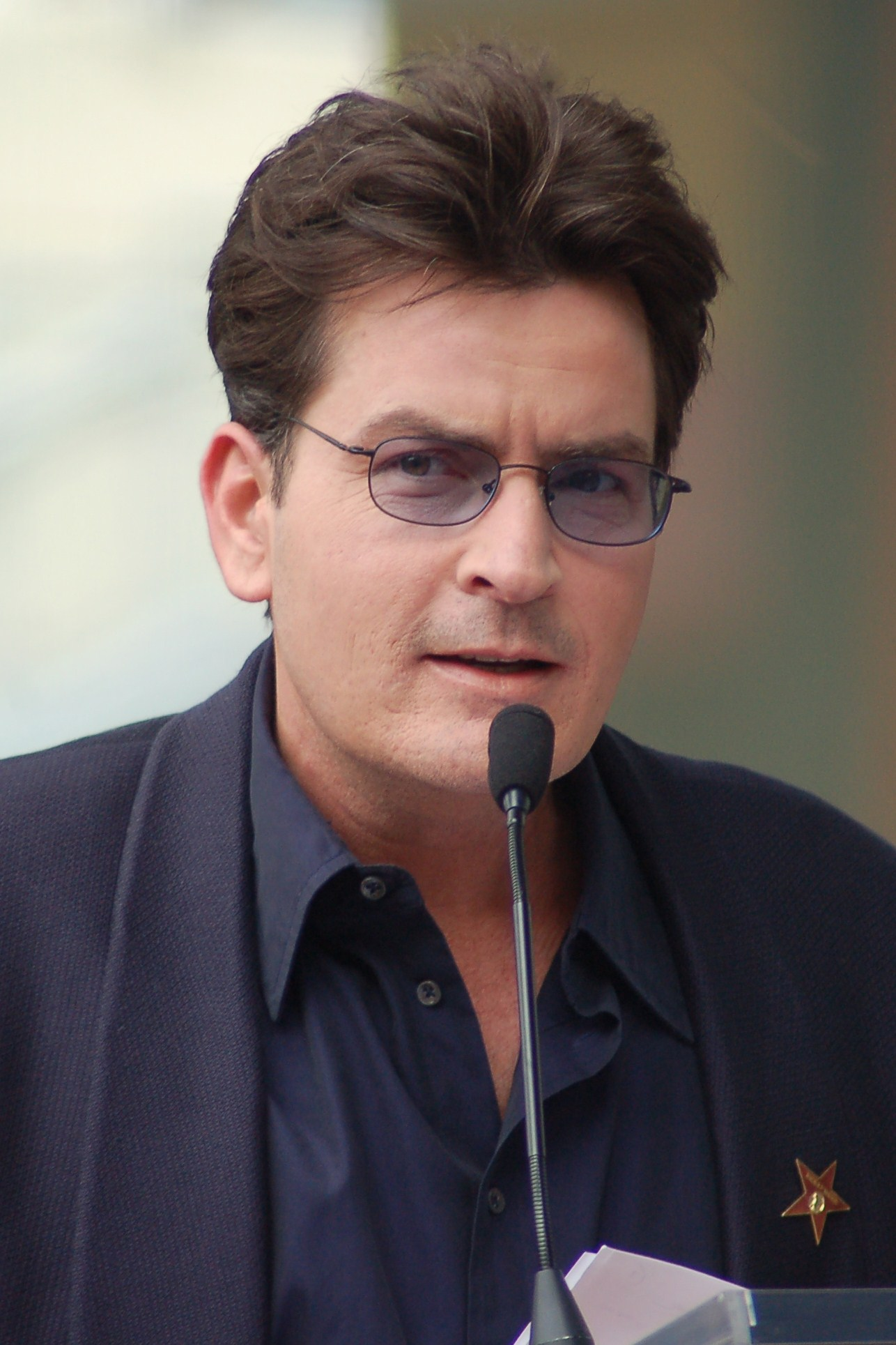 Charlie Sheen wearing black specs and black blazer.