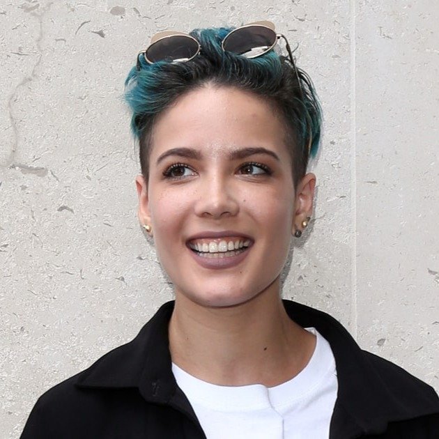 Halsey wearing a white t-shirt and black shirt, with her sunglasses ticked in her green hair