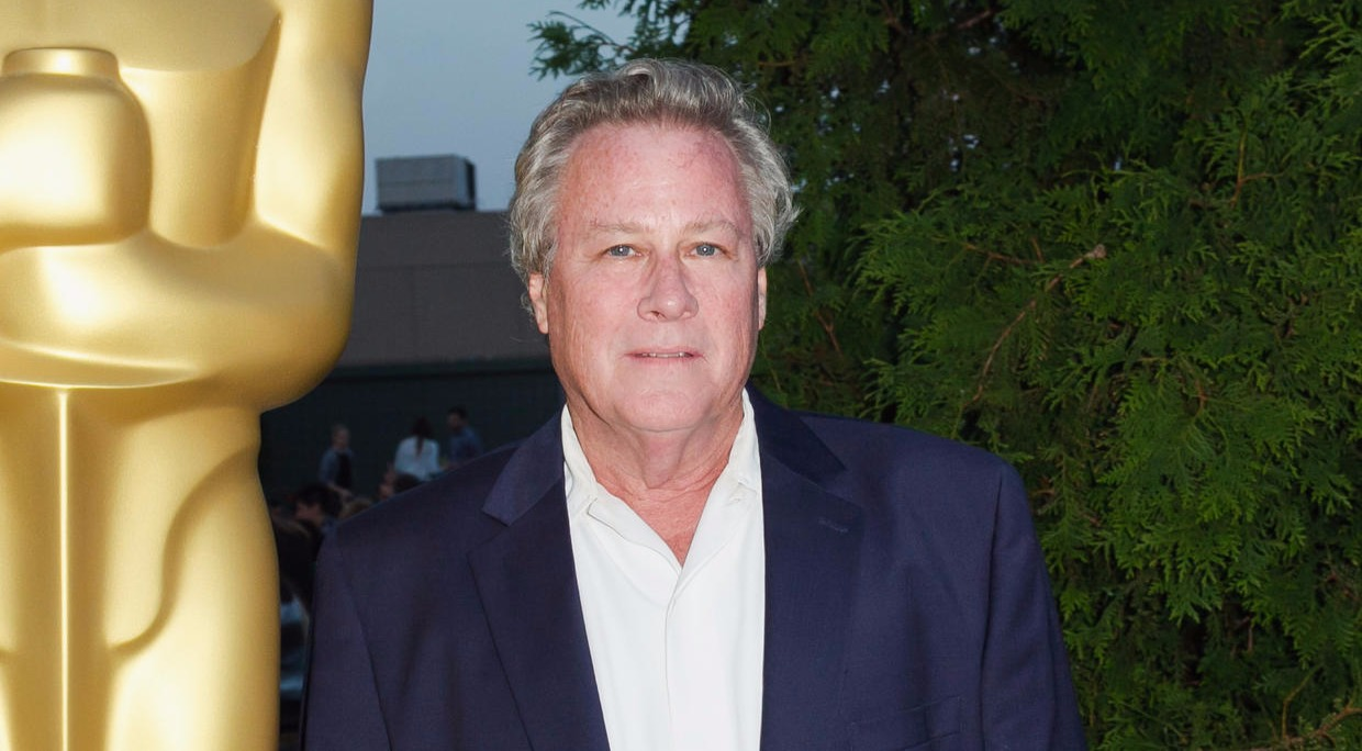 Home Alone actor John Heard poses in front of a Academy Awards bust