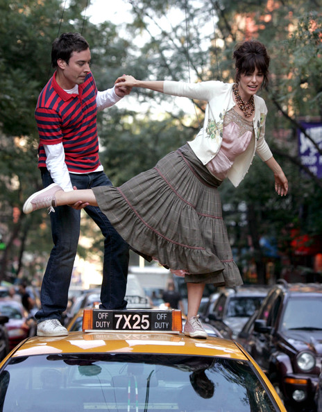 Jimmy Fallon and Parker Posey are practicing  dance in the roof of a taxi.