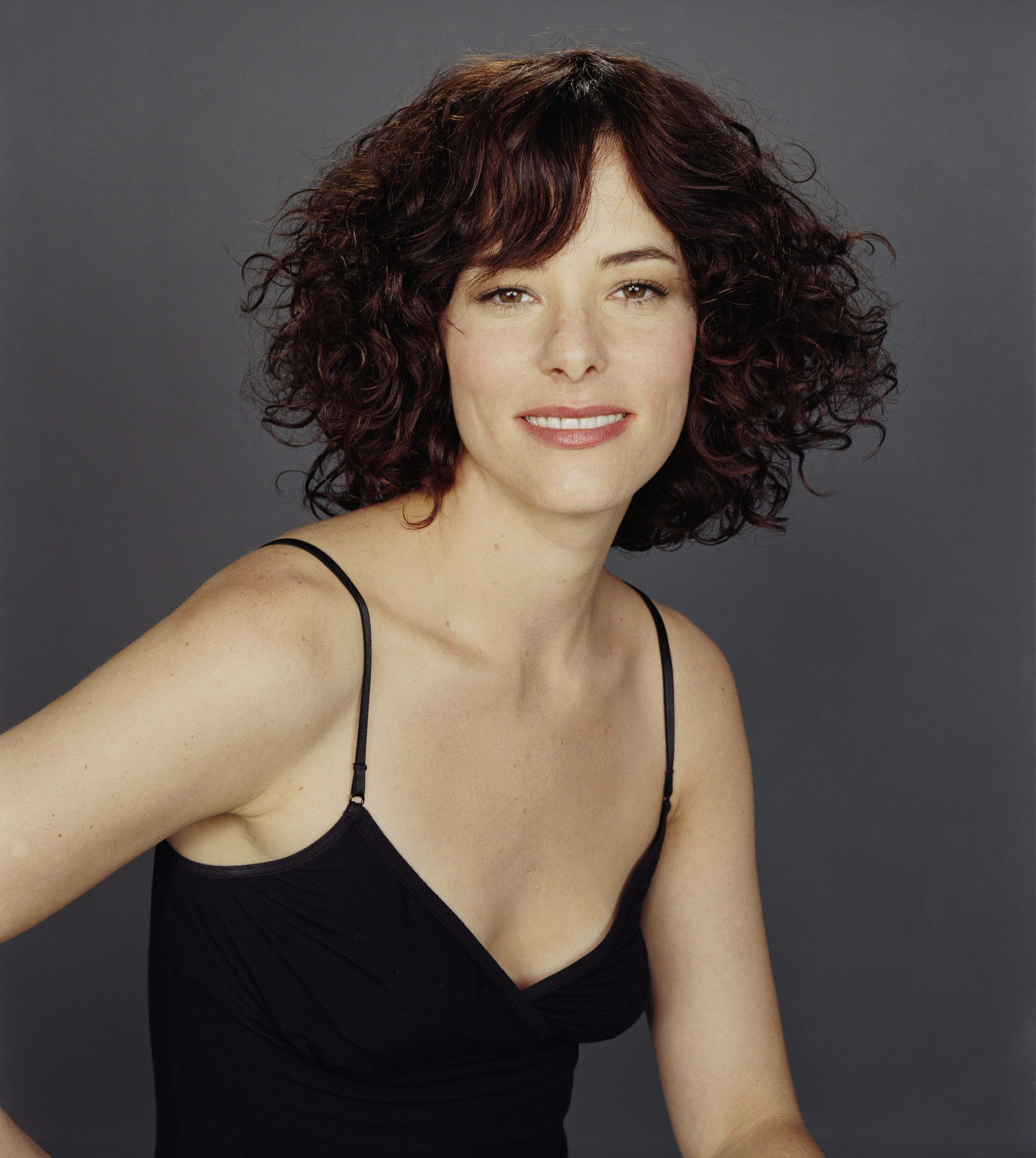 Parker Posey gives a sexy look in her cleavage showing dress and messy hair.