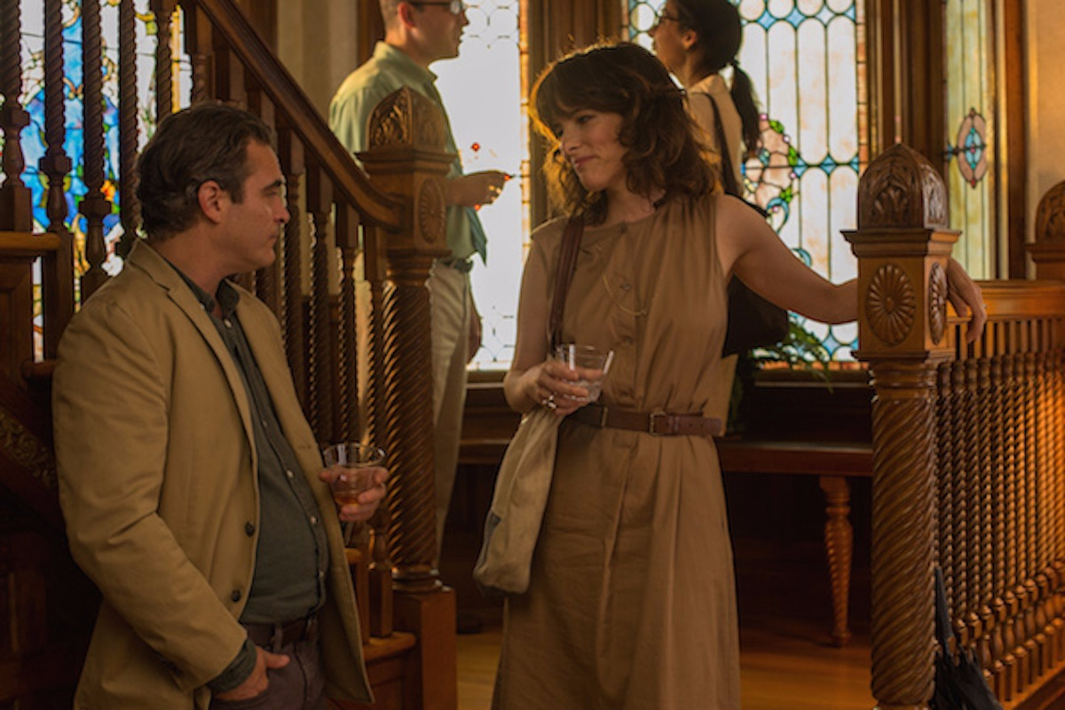 Parker Posey is standing in staircase in conversation with a man they both are holding a drinking glass the background make the scene look like they are in a party.