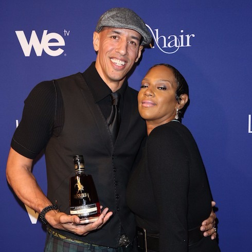 Jackie Christie poses with her husband Doug Christie at WE TV's L.A. Hair Season 3 Premiere. Doug has a bottle of Cognac Bossard on his hand.