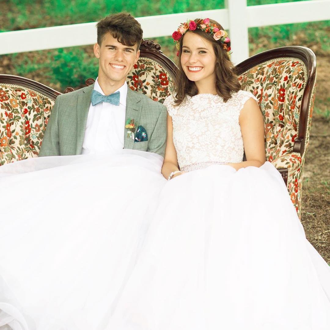 Willie Robertson's son John Luke and Mary Kate's wedding photo. The bride and groom are sitting next to each other at a table.