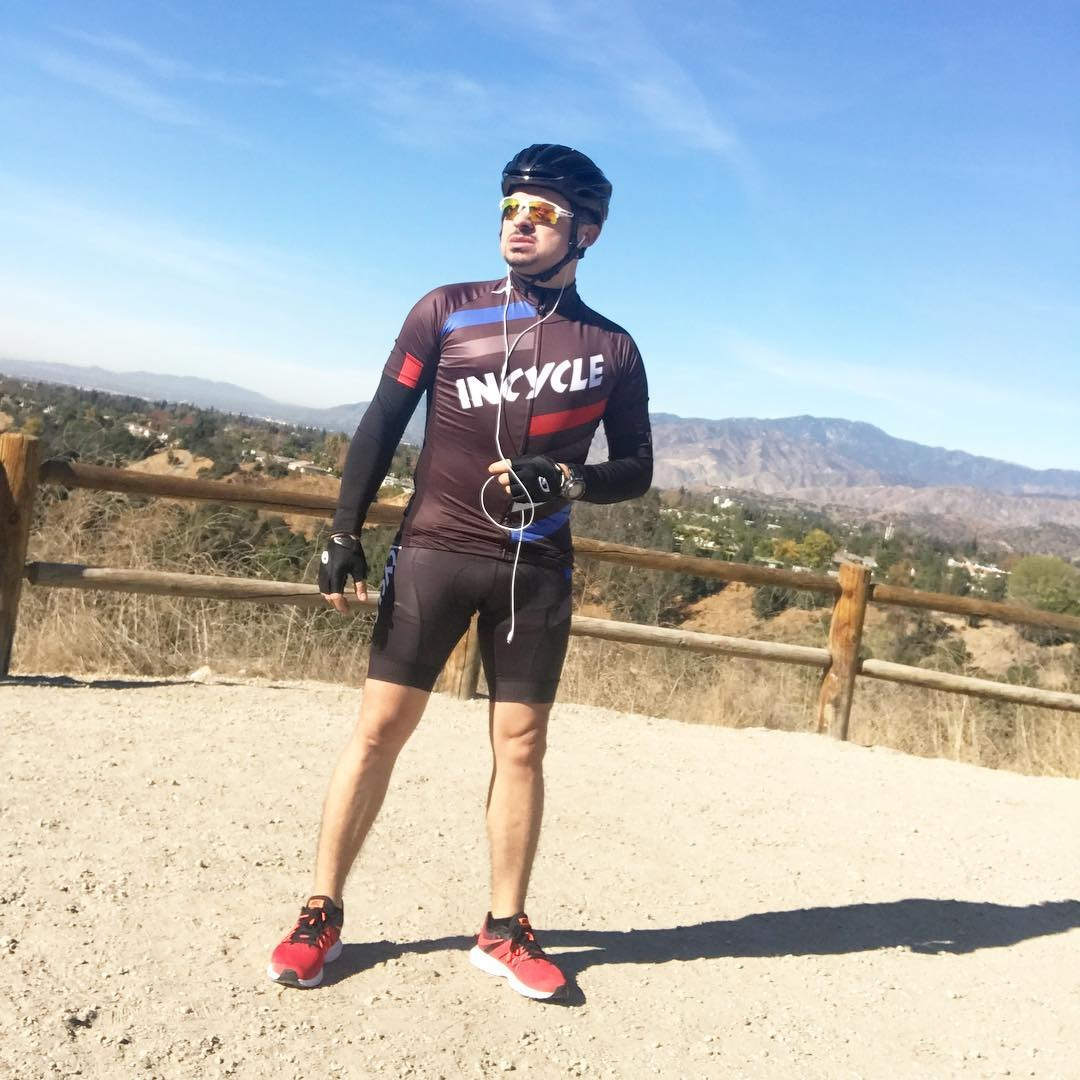 Larry Hernandez is standing in his athletic gear, with his bicycle helmet on and an earphone.
