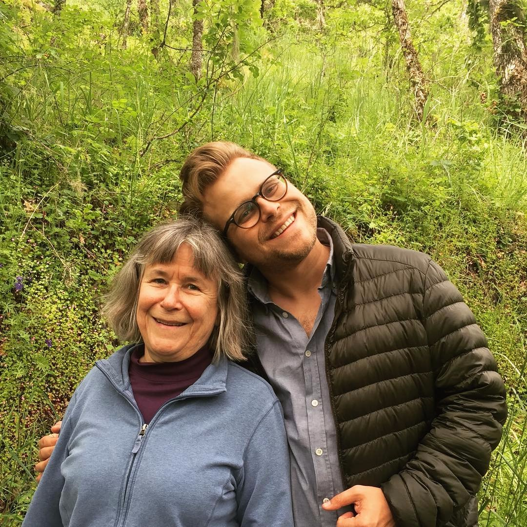Adam Conover hugs his mother sideways, they are both smiling.