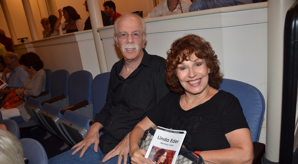 Joy Behar and Steve Janowitz sitting and looking sideways at the camera