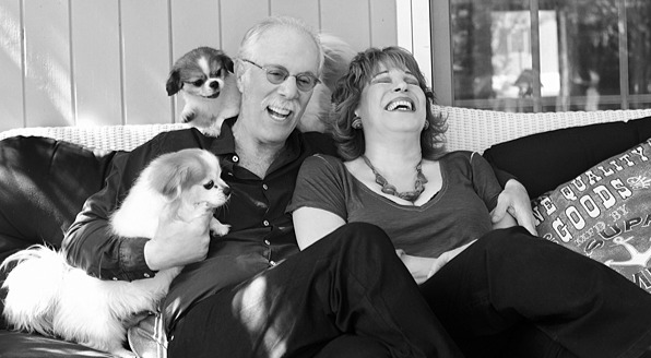 Joy Behar and Steve Janowitz sitting on the couch laughing, Janowitz is holding a dog and another dog is peeping from behind
