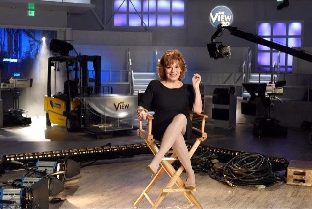 Joy Behar sitting on a director's chair, crossing her legs, she's in a studio