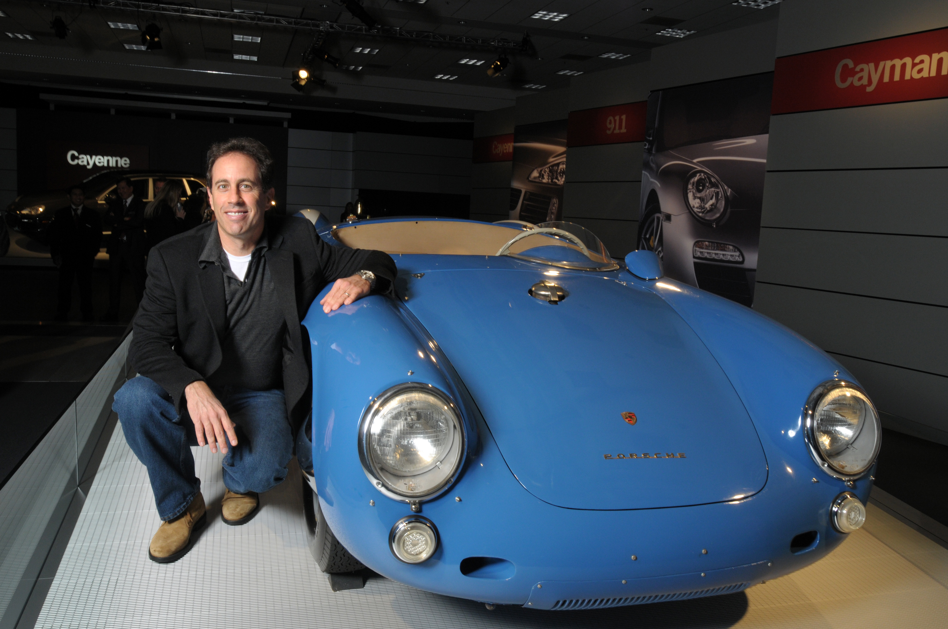 Jerry Seinfeld poses beside his Porsche 550 spyder in a showroom. The beautiful car has a rich light blue body paint