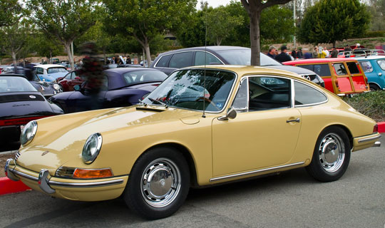 The cream colored Porsche 911 from 1966 is a two seater with a radio large antenna in the body