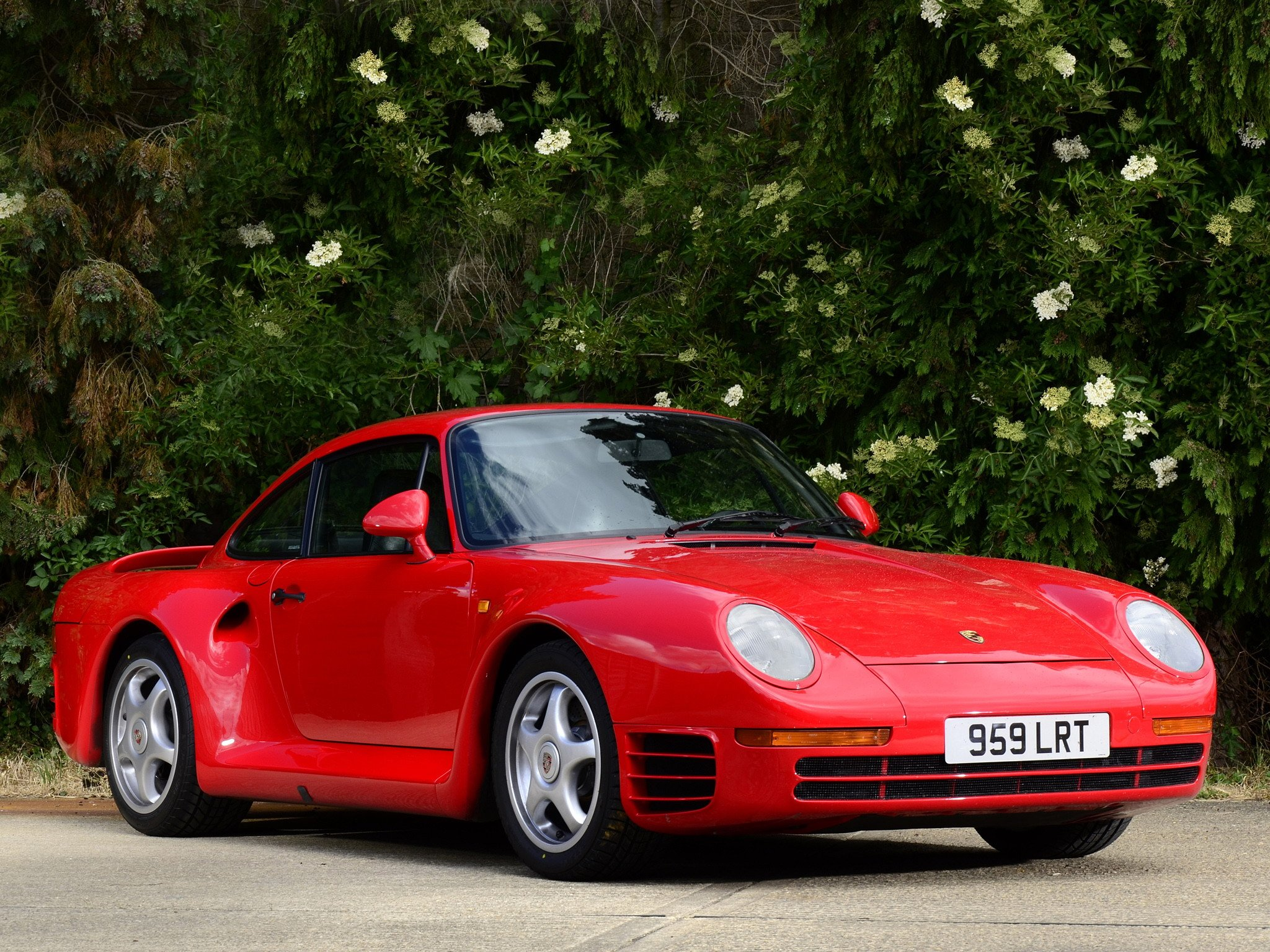 A picture of the Porsche 959 in the public. The beautiful car has a red body and is a two seater