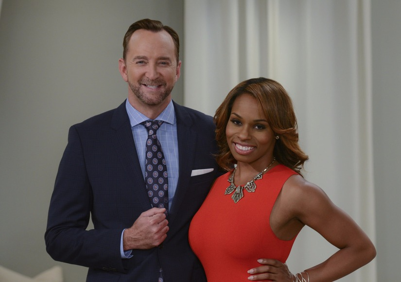 Clinton Kelly and Devyn Simone are standing close to each other. Clinton is raising his hand up to his waist level, making a fist. Devyn is resting her hand on her waist.