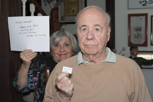 Tim Conway holding a small piece of paper. His wife is in the back holding a big sheet of paper