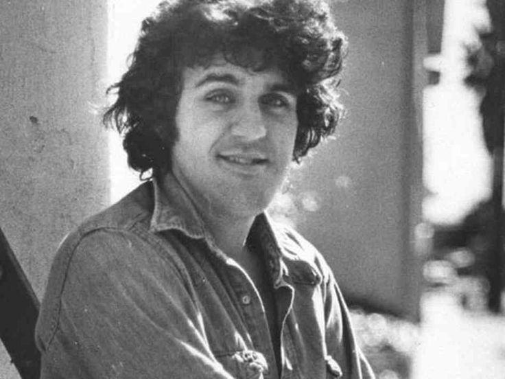 Jay Leno looking towards the camera with a smile. He has a big chin and black hair.