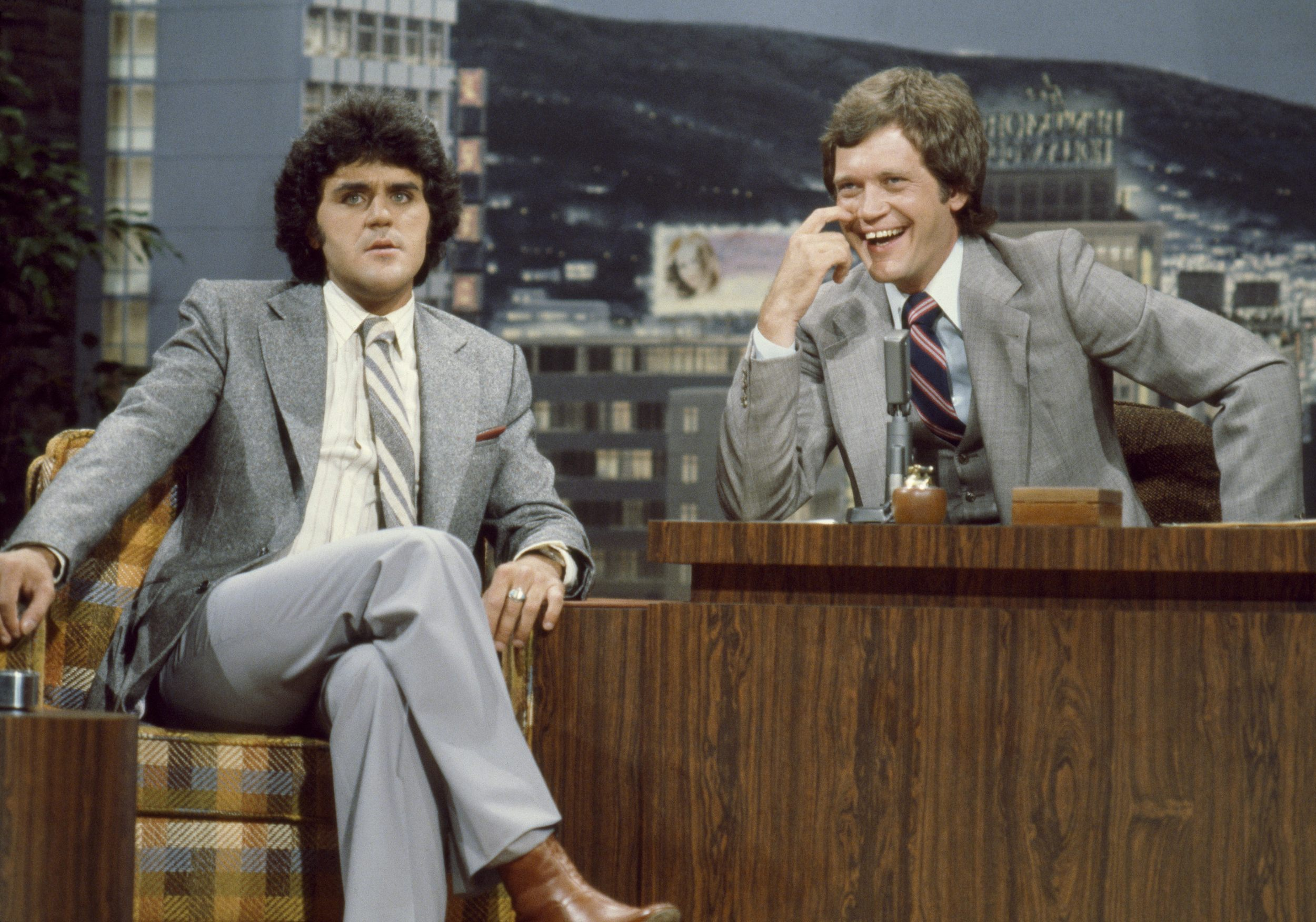Jay Leno sits to the left of David Letterman. Jay Leno has his legs crossed while David Letterman has his hand on the table.