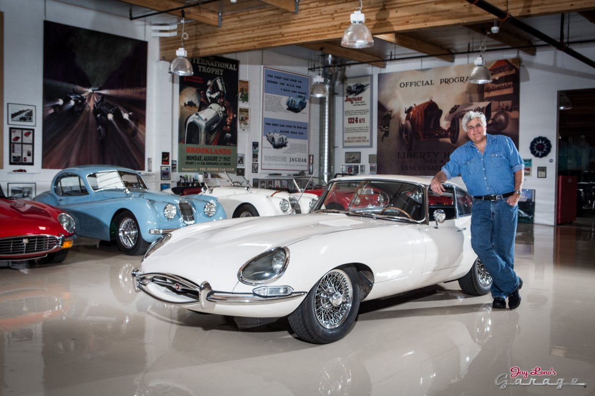 Jay Leno stands beside his Jaguar with his hand rested in the hood of the white car.