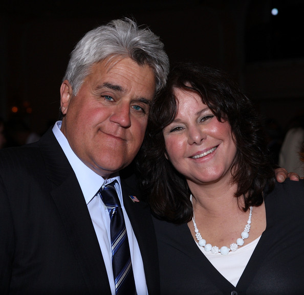 Jay Leno hugs his wife Mavis Leno while they both look at the camera