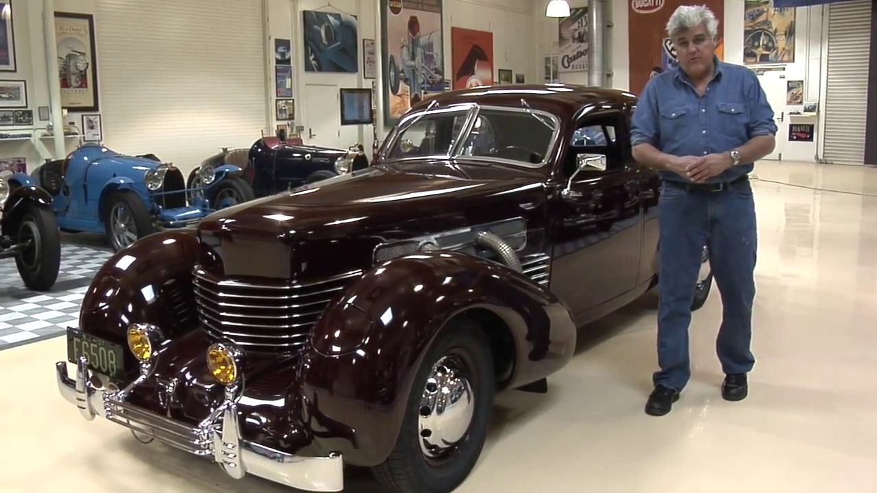 Jay Leno standing next to his ride, Cord 812