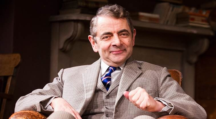 Rowan Atkinson sitting on the couch with a smile on his face. He is wearing grey and white dotted suit. He is popularly known as Mr. Bean.