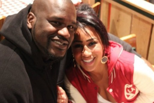 Nicole Hoopz is sitting next to Shaquille O'Neal. The two are looking straight at the camera with a faint smile. Shaquille has wrapped his arms around Hoopz. She is wearing a red and white hoodie while Shaq is wearing black hoodie.