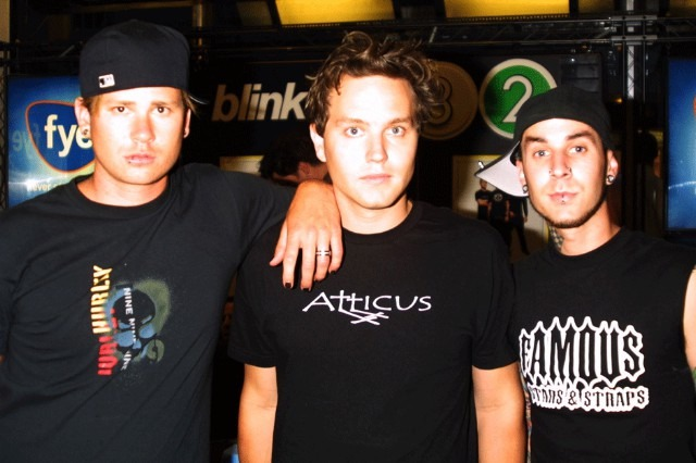 Blink 182 from left to right (Tom Delonge, Mark Hoppus, and Travis Barker). All following the dress coke black and facing the camera with serious faces.